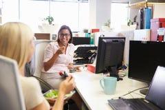Två kvinnor som äter lunch på arbete Royaltyfri Fotografi