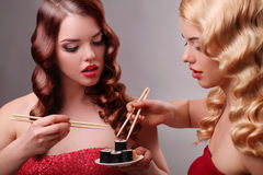 Två kvinnor som äter sushirullar Fotografering för Bildbyråer