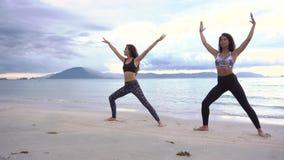 Två kvinnor som öva yoga på stranden stock video