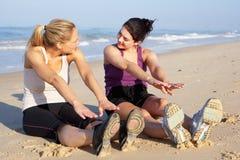 Två kvinnor som övar på strand Arkivfoto