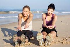 Två kvinnor som övar på strand Fotografering för Bildbyråer