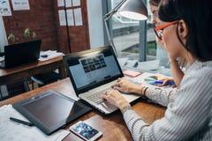 Två kvinnor som arbetar på den nya websitedesignen som väljer bilder genom att använda bärbara datorn som surfar internet Royaltyfria Foton