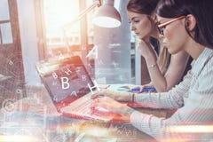 Två kvinnor som arbetar på den nya websitedesignen som väljer bilder genom att använda bärbara datorn som surfar internet arkivbilder