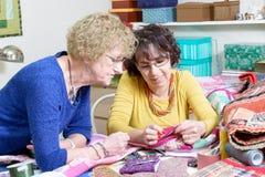 Två kvinnor som arbetar på deras patchwork Royaltyfria Bilder
