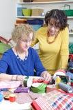 Två kvinnor som arbetar på deras patchwork Arkivbilder