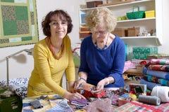 Två kvinnor som arbetar på deras patchwork Arkivbild