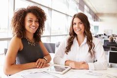 Två kvinnor som arbetar på en arkitekt? s-kontor som ser till kameran Royaltyfria Bilder
