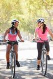 Två kvinnor som cyklar på den förorts- gatan Royaltyfria Bilder