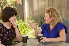 Två kvinnor som delar och pratar över kaffe Royaltyfri Bild
