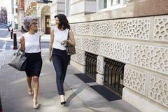 Två kvinnor som går i gatan som talar, full längd royaltyfri bild