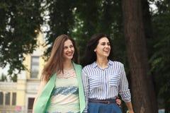 Två kvinnor som går i sommaren, parkerar royaltyfria foton
