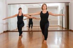 Två kvinnor som gör en kondition, exercisen i synchrony Royaltyfria Bilder