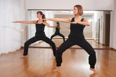 Två kvinnor som gör en kondition, exercisen i synchrony Fotografering för Bildbyråer