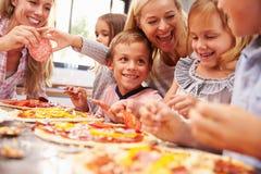 Två kvinnor som gör pizza med ungar royaltyfri bild