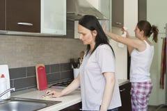 Två kvinnor som gör ren möblemanget Royaltyfri Bild