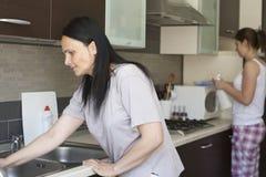 Två kvinnor som gör ren möblemanget Arkivfoton