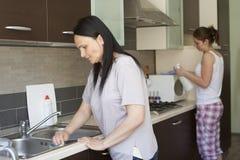 Två kvinnor som gör ren möblemanget Arkivfoto