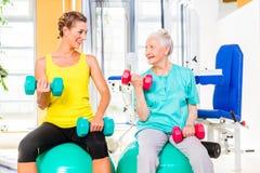 Två kvinnor som gör styrkasporten i konditionidrottshall Royaltyfri Fotografi
