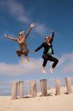 Två kvinnor som högt hoppar på stranden Arkivbilder