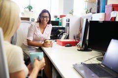 Två kvinnor som har ett kaffeavbrott på arbete Arkivbild
