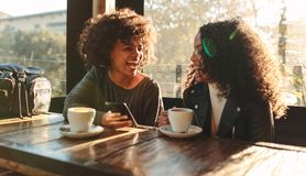 Två kvinnor som har gyckel på en coffee shop Arkivbild