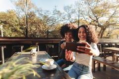 Två kvinnor som har gyckel som utomhus tar en selfie Royaltyfri Fotografi