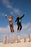 Två kvinnor som hoppar från en rad av poler på stranden Fotografering för Bildbyråer