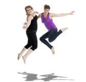 Två kvinnor som hoppar i luften. På white Royaltyfri Foto