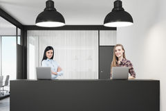 Två kvinnor som i regeringsställning står på ett mottagandeskrivbord Royaltyfri Bild
