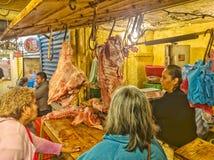 Två kvinnor som köper nytt grisköttkött från slaktare på marknaden i Teloloapan, Guerrero Liv i Mexico arkivbilder