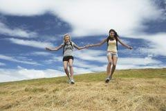 Två kvinnor som rymmer händer och hoppar over ner kullen Royaltyfria Foton