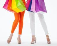 Två kvinnor som rymmer mångfärgade shoppingpåsar Arkivfoton
