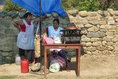 Två kvinnor som säljer mat på trottoaren Fotografering för Bildbyråer