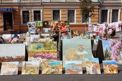 Två kvinnor som söker efter målningar på rea Arkivbild