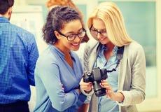 Två kvinnor som ser den digitala kameran på kontoret Royaltyfri Foto