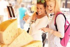 Två kvinnor som shoppar för ost på matmarknad Royaltyfria Foton