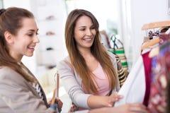 Två kvinnor som shoppar i en boutique Arkivbilder