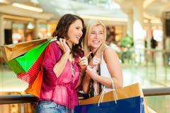 Två kvinnor som shoppar med påsar i galleria Arkivbild
