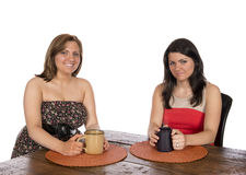 Två kvinnor som sitter ha kaffe på tabellen Royaltyfri Bild