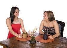 Två kvinnor som sitter ha kaffe på tabellen Arkivfoton