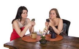 Två kvinnor som sitter kaffemobiltelefoner Royaltyfri Fotografi