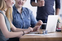 Två kvinnor som sitter med bärbara datorn royaltyfri bild