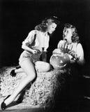 Två kvinnor som sitter på en bal av hö som snider en pumpa (alla visade personer inte är längre uppehälle, och inget gods finns L Royaltyfria Bilder