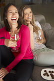 Två kvinnor som sitter på Sofa Watching TV som dricker vin Arkivfoto