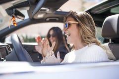 två kvinnor som sjunger i bilen arkivfoto