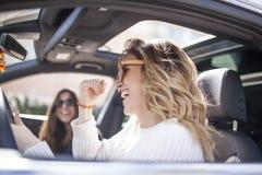 två kvinnor som sjunger i bilen royaltyfria bilder