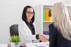 Två kvinnor som skakar händer, medan möta i kontoret Royaltyfria Bilder