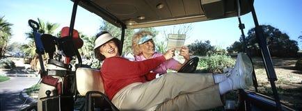 Två kvinnor som skrattar i golfvagn Fotografering för Bildbyråer