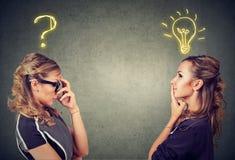Två kvinnor som tänker en, har en fråga en annan lösning med den ljusa kulan ovanför huvudet Royaltyfri Bild