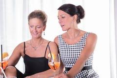 Två kvinnor som talar och har en drink royaltyfri fotografi